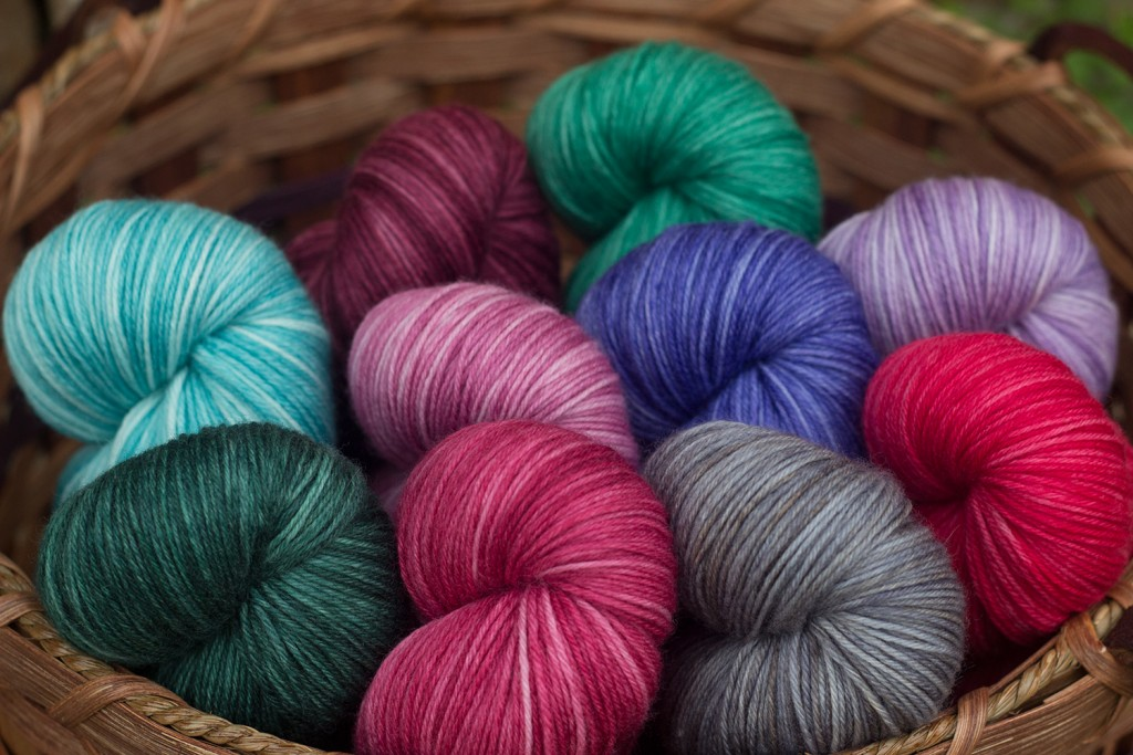 A basket full of Round Table Yarns in the Camelot base, which is a fingering weight MCN.